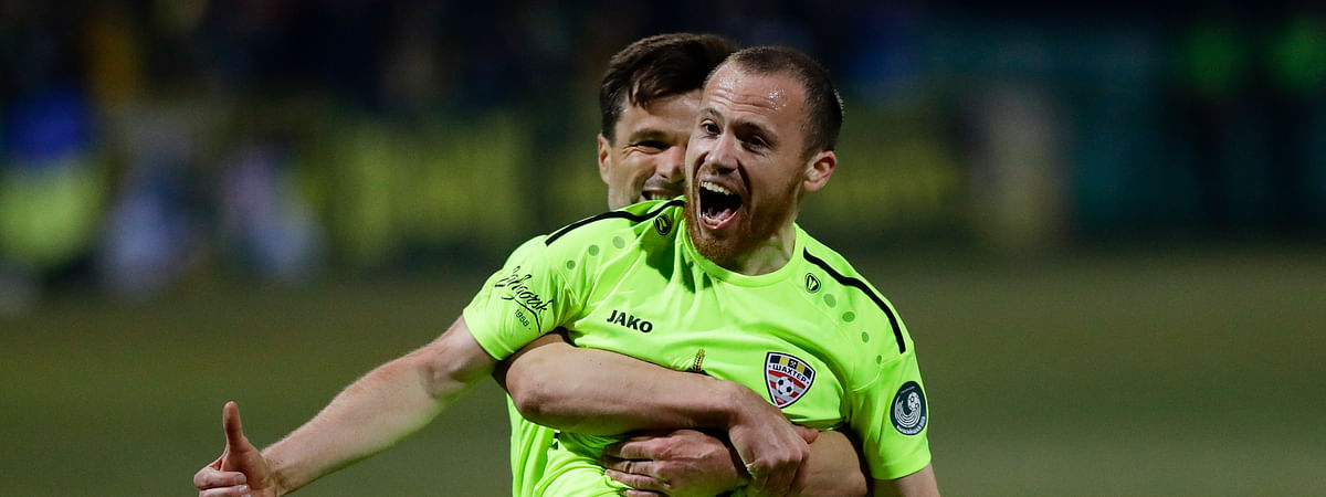 In this photo taken on Saturday, March 28, 2020, Shakhter's Sergei Balanovich, foreground, and his teammate Azdren Llullaku celebrate after scoring their side's goal during the Belarus Championship soccer match between Gorodeya and Shakhter in the town of Gorodeya, Belarus.