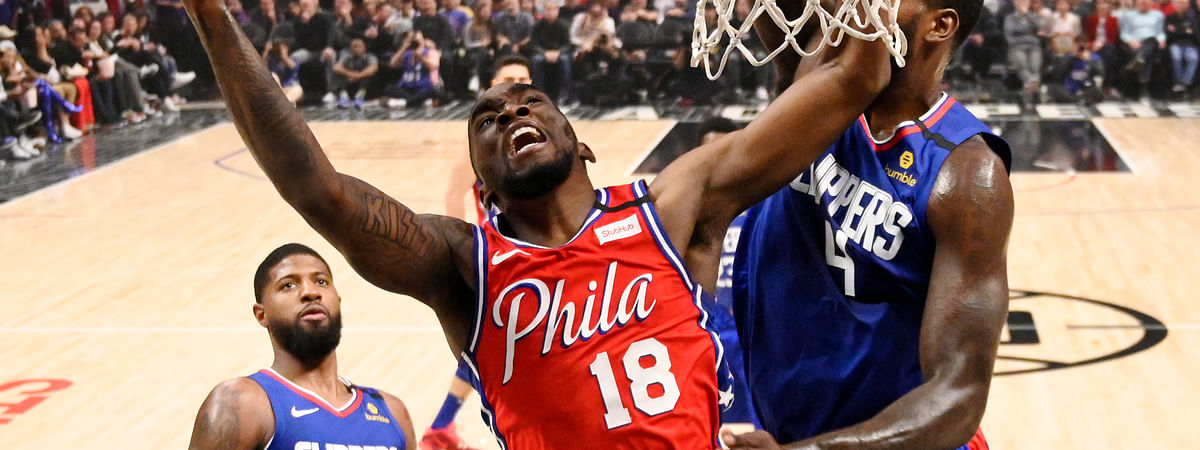Philadelphia 76ers guard Shake Milton, center, shoots as Los Angeles Clippers forward JaMychal Green, right, defends and guard Paul George watches during the first half of an NBA basketball game Sunday, March 1, 2020, in Los Angeles. (AP Photo/Mark J. Terrill)