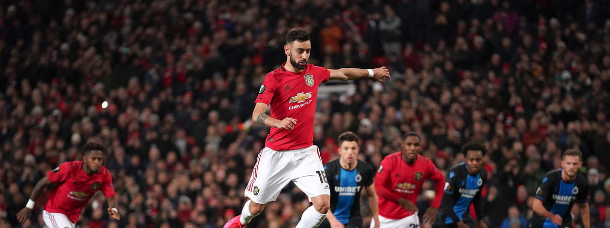 Manchester United's Bruno Fernandes, center, scores his side's opening goal from the penalty spot during the round of 32 second leg Europa League soccer match between Manchester United and Brugge at Old Trafford in Manchester, England, Thursday, Feb. 27, 2020.