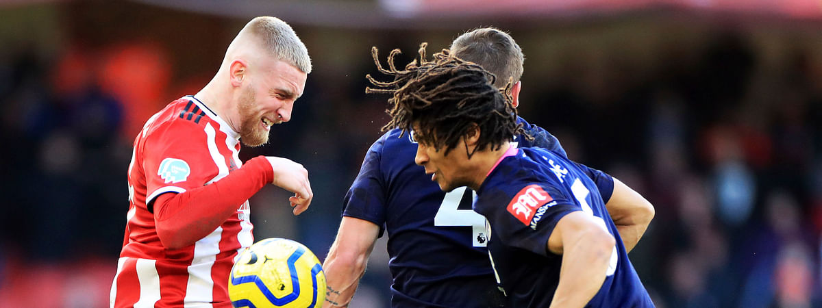 Sheffield United's Oliver McBurnie, left, and Bournemouth's Nathan Ake battle for the ball during the English Premier League soccer match at Bramall Lane, Sheffield, England, Sunday Feb. 9, 2020.
