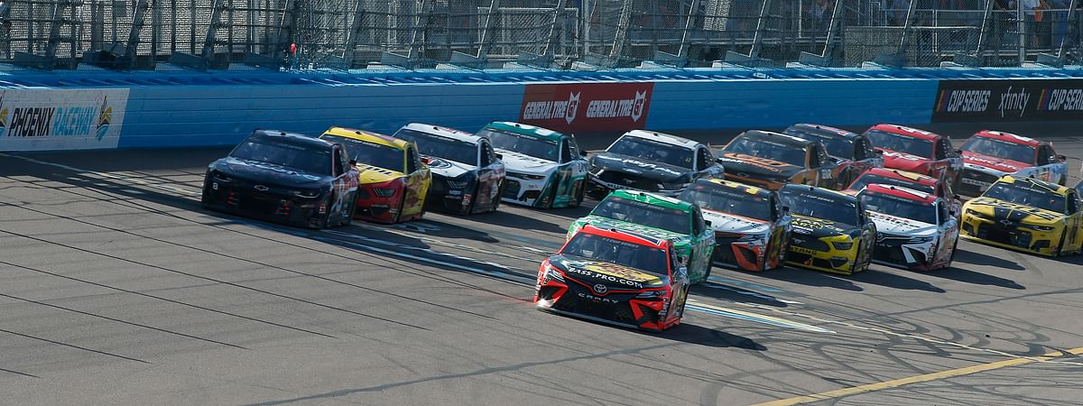 Martin Truex Jr. (19) leads the field through Turn 4 on a restart during the NASCAR Cup Series auto race at Phoenix Raceway, Sunday, March 8, 2020, in Avondale, Ariz.