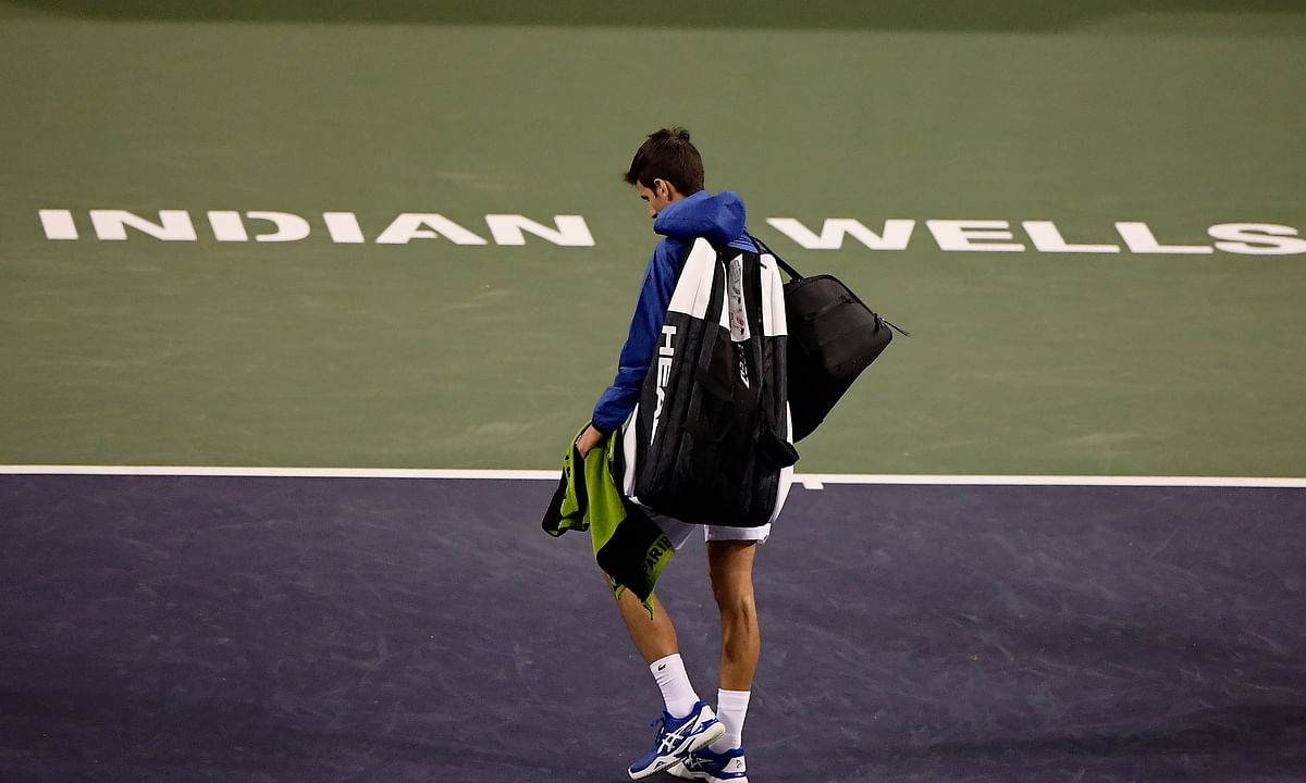 In this Monday, March 11, 2019, file photo, Novak Djokovic, of Serbia, walks off the court during a rain break in his match against Philipp Kohlschreiber, of Germany, at the BNP Paribas Open tennis tournament in Indian Wells, Calif. The BNP Paribas Open tennis tournament, set to begin Wednesday, March 11, 2020, has been postponed after a case of coronavirus was confirmed in the Coachella Valley.