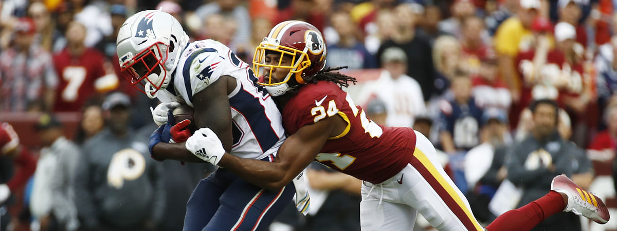 In this Oct. 6, 2019, file photo, Washington Redskins cornerback Josh Norman (24) tackles New England Patriots running back Sony Michel (26) during the second half of an NFL football game in Landover, Md. Norman struggled to live up to the $75 million, five-year contract he signed in 2016 after an All-Pro season in Carolina. He was let go with one year left on that deal.