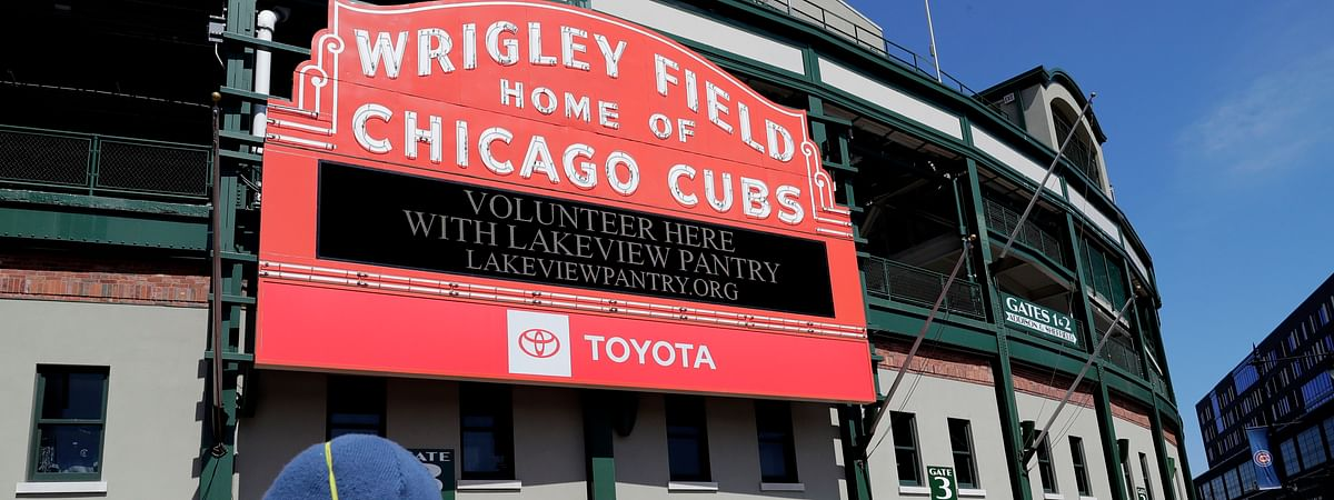 In this April 16, 2020, file photo, Wrigley Field's marquee displays Lakeview Pantry volunteer information in Chicago. With no games being played, recent sports headlines have centered around hopes and dreams — namely, the uncharted path leagues and teams must navigate to return to competition in the wake of the pandemic.