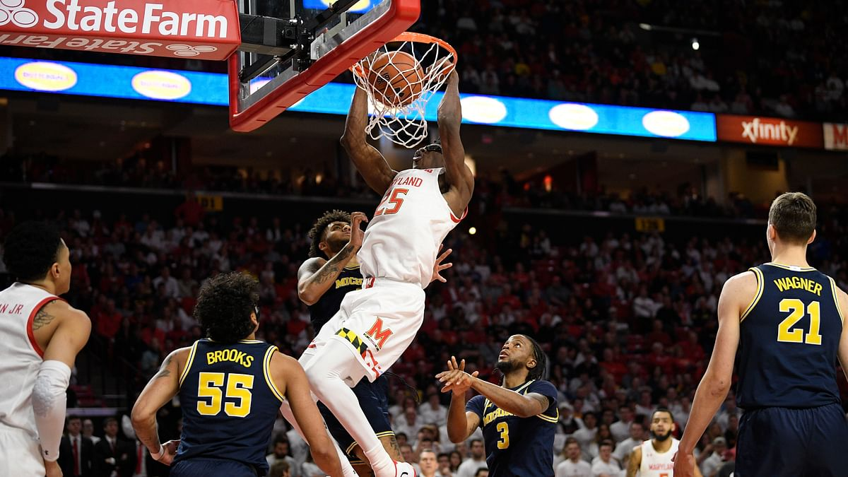 Maryland forward Jalen Smith (25) dunks against Michigan guard Eli Brooks (55), guard Zavier Simpson (3) and forward Isaiah Livers, back, during the second half of an NCAA college basketball game, Sunday, March 8, 2020, in College Park, Md.