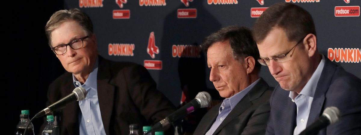 From left, in a Jan. 15, 2020, file photo, Boston Red Sox owner John Henry, chairman Tom Werner and CEO Sam Kennedy react during a news conference at Fenway Park in Boston. The Boston Red Sox were stripped of their second-round pick in this year's amateur draft by Major League Baseball for breaking video rules in 2018 and former manager Alex Cora was suspended through the 2020 postseason for his conduct as bench coach with the Houston Astros the previous year.