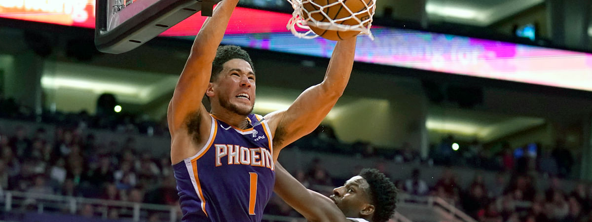 In this Jan. 5, 2020, file photo, Phoenix Suns guard Devin Booker (1) dunks over Memphis Grizzlies forward Jaren Jackson Jr. in the second half of an NBA basketball game in Phoenix. Booker won the NBA 2K20 Players Tournament on Saturday, April 11, 2020, sweeping Suns teammate Deandre Ayton in the best-of-three final.