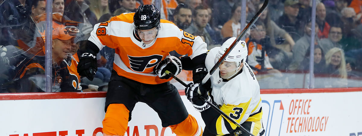 In this Jan. 21, 2020, file photo, Philadelphia Flyers' Tyler Pitlick, left, tries to jump past Pittsburgh Penguins' Jack Johnson during the second period of an NHL hockey game in Philadelphia. The latest chapter of The Battle of Alberta is on hold. So's the potential renewal of the Pennsylvania rivalry between the Penguins and Flyers. It's unclear when or if the coronvirus pandemic-delayed NHL playoffs -- which were supposed to begin Wednesday -- will be played or what form they'll resemble.