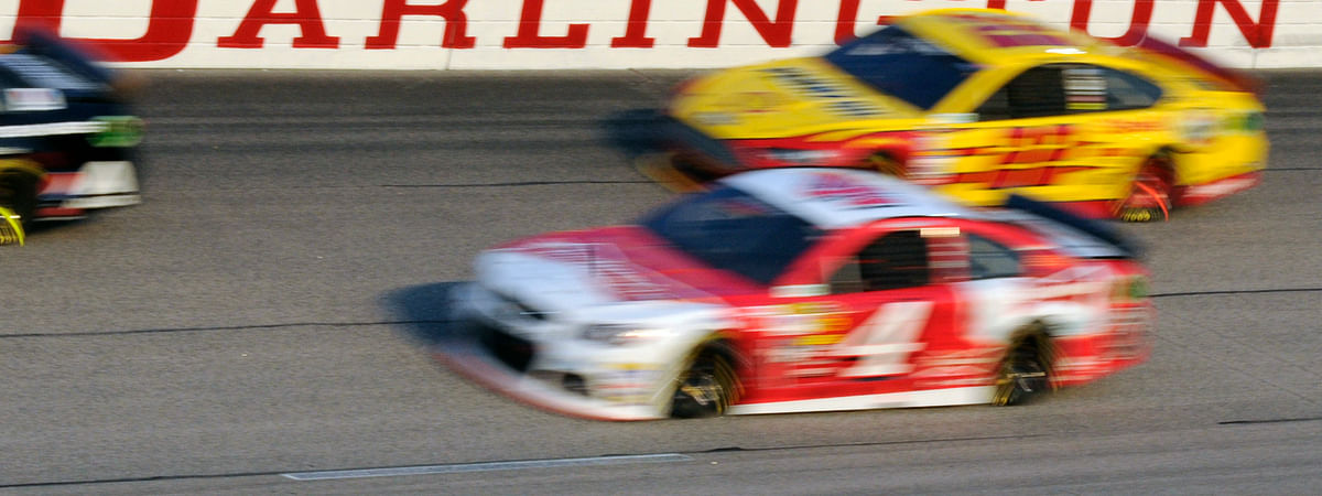 In this April 12, 2014, file photo, Kevin Harvick (4) and Joey Logano (22) race during a NASCAR Sprint Cup series auto race at Darlington Raceway in Darlington, S.C. NASCAR will get its season back on track starting May 17 at Darlington Raceway in South Carolina without spectators, and the premier Cup Series plans to race four times in 10 days at a pair of iconic tracks.