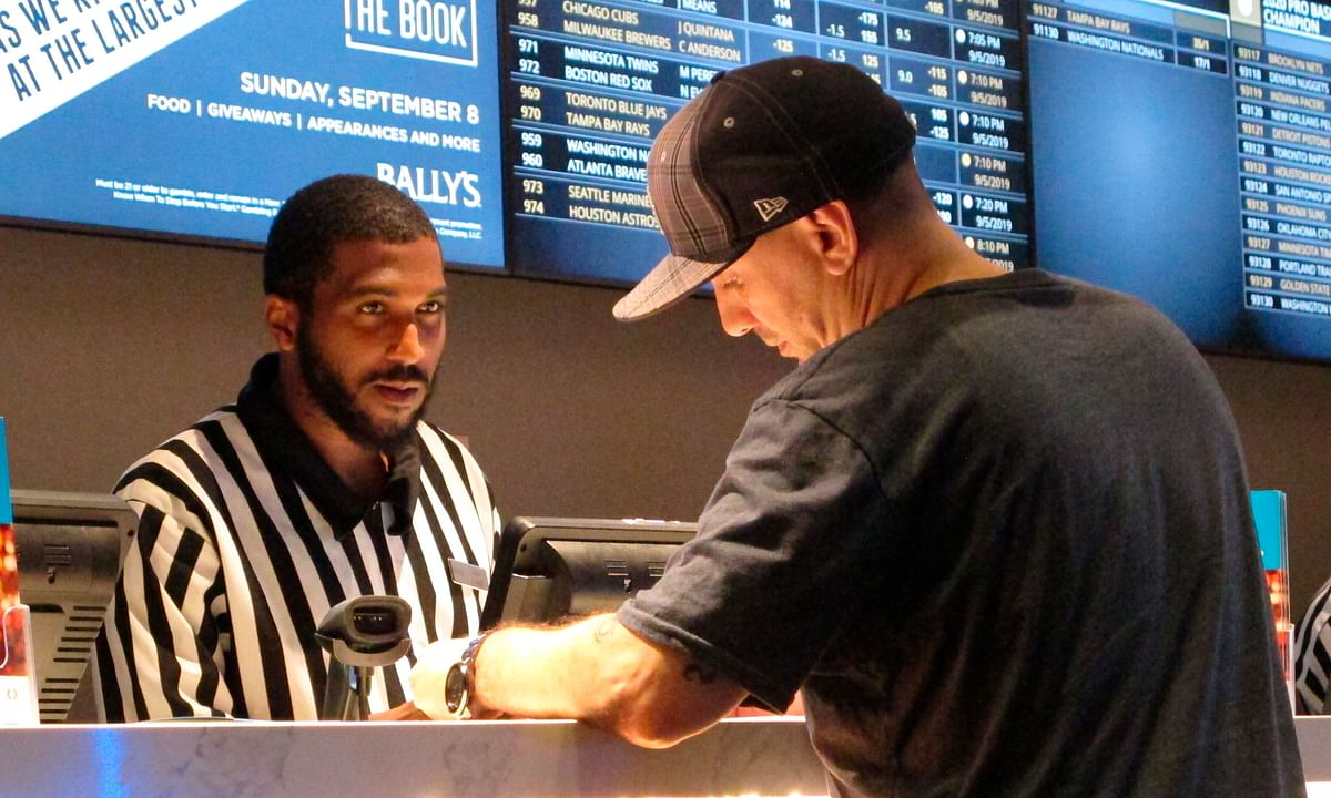 In this Sept. 5, 2019, file photo, a gambler making a sports bet at Bally's casino in Atlantic City, N.J. The NFL draft starting on Thursday, April 23, 2020, is expected to be the most heavily wagered-on draft ever, mainly because virtually all major sporting events have been postponed due to the coronavirus outbreak.