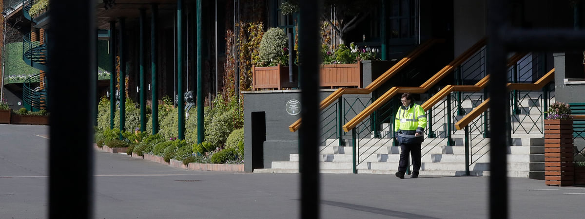 A security guard inside the main gates to Wimbledon as it is announced the the Wimbledon tennis Championships for 2020 has been cancelled due to the coronavirus in London, Wednesday, April 1, 2020. The new coronavirus causes mild or moderate symptoms for most people, but for some, especially older adults and people with existing health problems, it can cause more severe illness or death.(AP Photo/Kirsty Wigglesworth)