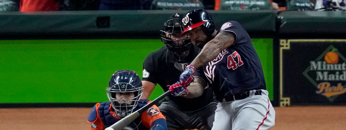 """In this Oct. 30, 2019, file photo, Washington Nationals' Howie Kendrick hits a two-run home run against the Houston Astros during the seventh inning of Game 7 of the baseball World Series in Houston. To many National League fans, the scribble of """"DH"""" on the lineup card sullies the whole stadium. To lots of American League fans, the sight of a pitcher touching a Louisville Slugger is a total affront to the diamond."""