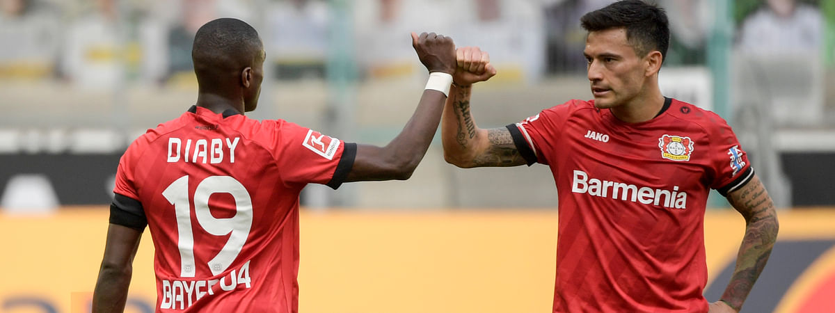 Leverkusen's French forward Moussa Diaby, left, and teammate Charles Mariano Aranguiz celebrate after the German Bundesliga soccer match between Borussia Moenchengladbach and Leverkusen, in Moenchengladbach, Germany, Saturday, May 23, 2020.