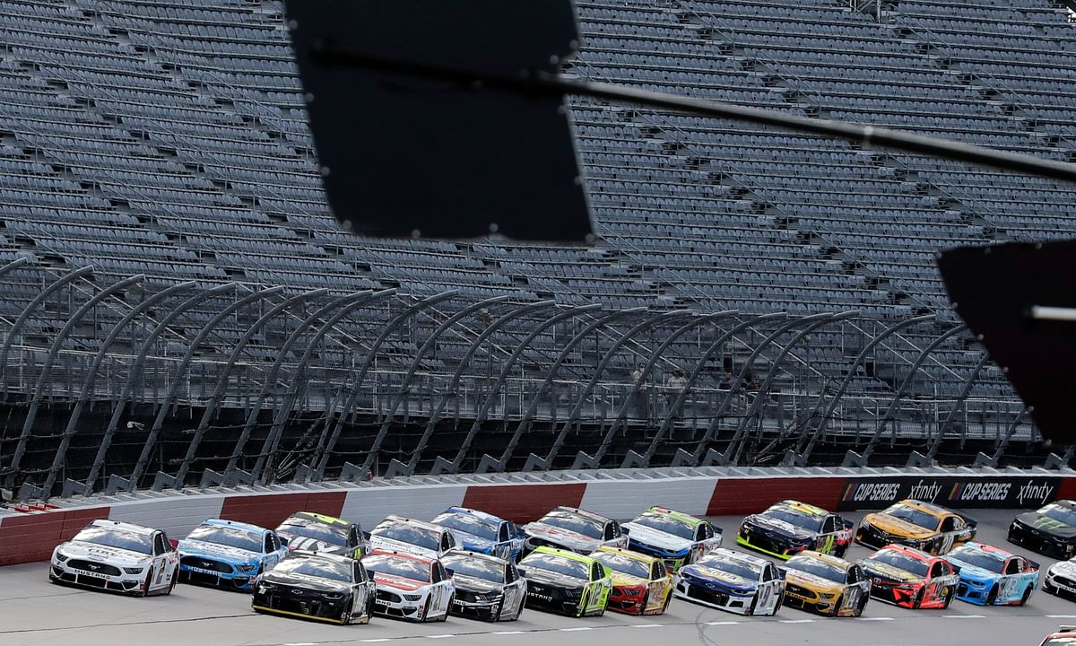 Cars approach the starting line in front of empty stands to start the NASCAR Cup Series auto race Sunday, May 17, 2020, in Darlington, S.C. (AP Photo/Brynn Anderson)
