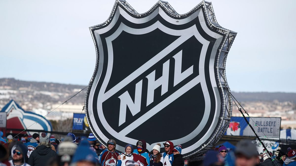 In this Saturday, Feb. 15, 2020, file photo, fans pose below the NHL league logo at a display outside Falcon Stadium before an NHL Stadium Series outdoor hockey game between the Los Angeles Kings and Colorado Avalanche, at Air Force Academy, Colo. The NHL Players' Association's executive board is voting on a 24-team playoff proposal as the return-to-play format, a person with knowledge of the situation told The Associated Press, late Thursday, May 21, 2020.