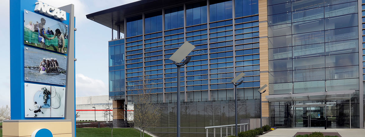 In this is an April 25, 2018, file photo, NCAA headquarters in Indianapolis is viewed. College sports programs are already being cut and more are likely on the chopping block. The coronavirus pandemic has triggered fears of an economic meltdown on campuses around the country. The cancellation of the NCAA men's basketball tournament cost schools $375 million and more losses are expected, especially if football season is disrupted in the fall.