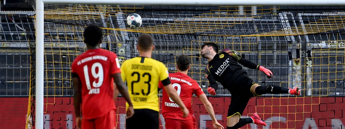 Dortmund's goalkeeper Roman Buerki, right, fails to stop a shot by Munich's Joshua Kimmich during the German Bundesliga soccer match between Borussia Dortmund and FC Bayern Munich in Dortmund, Germany, Tuesday, May 26, 2020.