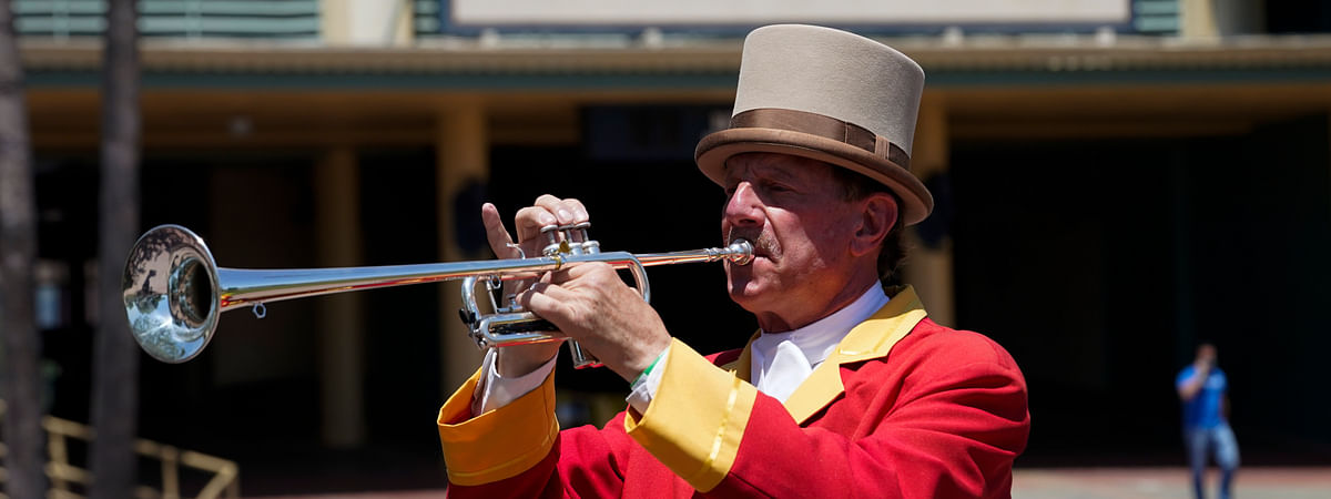 "In this Friday, May 22, 2020 photo, bugler Jay Cohen blows ""Call to the Post"" to the empty grandstand, a tradition maintained for those watching via simulcast, during a day of horse racing at Santa Anita Park in Arcadia, Calif. Horse racing returned to the track after being idled for one and a half months because of public health officials' concerns about the coronavirus pandemic."