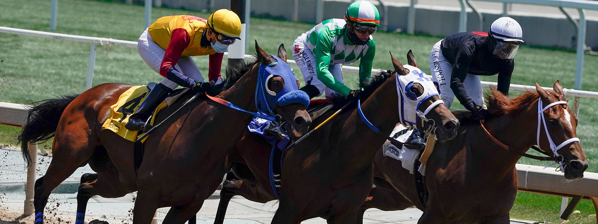 In this Friday, May 22, 2020 photo, jockeys wearing face masks ride in the first horse race at Santa Anita Park in Arcadia, California.