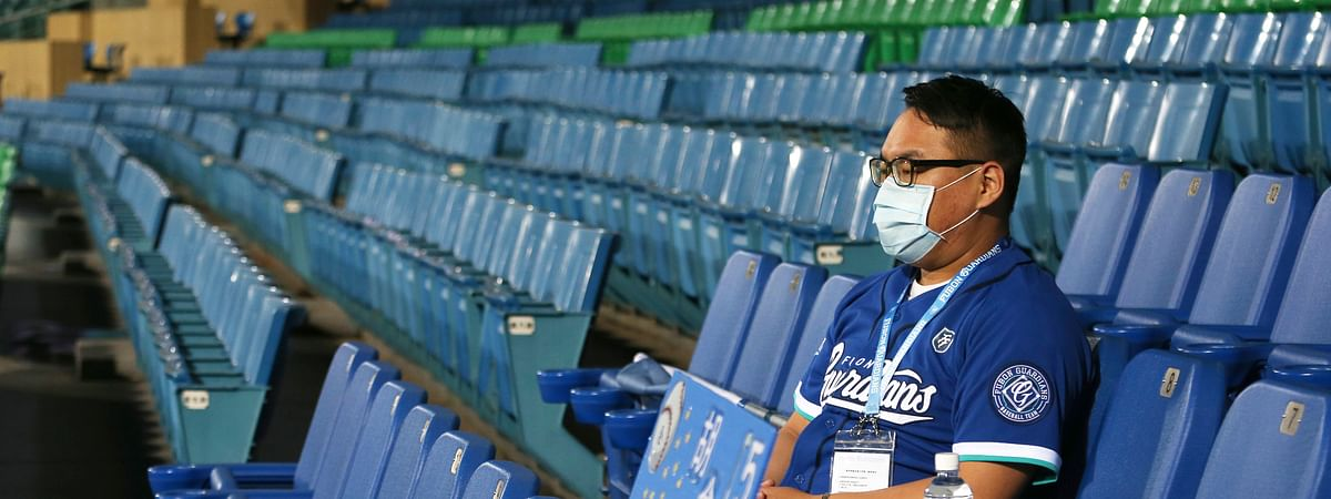 In this Friday, April 24, 2020, photo, a staff member of Chinatrust Brothers sits on the stands during a game against Fubon Guardians with no audience at Xinzhuang Baseball Stadium in New Taipei City, Taiwan, Friday, April 24, 2020. Taiwan has relatively few cases of COVID-19, so the league decided it was safe to let in players, coaches, cheerleaders, costumed mascots, face mask-wearing batboys and the media.