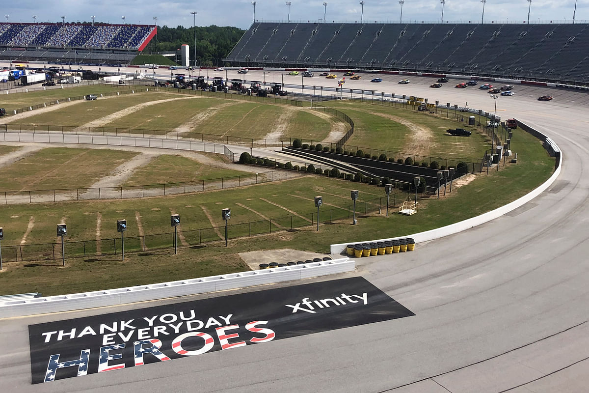 Cars go through a turn past a sign thanking people working during the coronavirus pandemic at Darlington Raceway Sunday, May 17, 2020, in Darlington, S.C. NASCAR, which has been idle for 10 weeks because of the pandemic, made its return with the Real Heroes 400 Nascar Cup Series auto race.