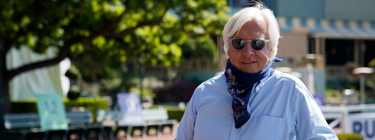 In this Friday, May 22, 2020 photo, Bob Baffert, two-time Triple Crown-winning trainer, lowers his bandana during an interview while keeping his distance at Santa Anita Park in Arcadia, Calif.