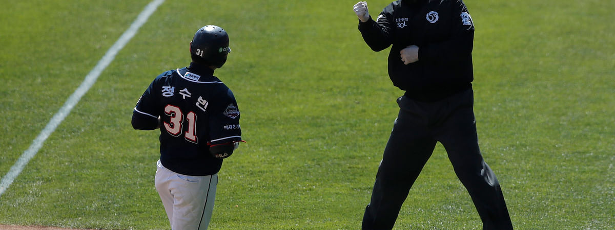 First base umpire Lee Gye-sung, right, wearing a mask and gloves as a precaution against the new coronavirus calls Doosan Bears' Jung Soo-bin out during the pre-season baseball game between Doosan Bears and LG Twins in Seoul, South Korea, Tuesday, April 21, 2020.