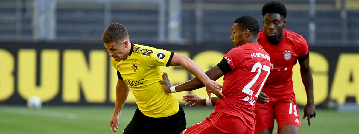 Munich's David Alaba, center, and Alphonso Davies, right, challenge for the ball with Dortmund's Thorgan Hazard, left, during the German Bundesliga soccer match between Borussia Dortmund and FC Bayern Munich in Dortmund, Germany, Tuesday, May 26, 2020. The German Bundesliga is the world's first major soccer league to resume after a two-month suspension because of the coronavirus pandemic. (Federico Gambarini/DPA via AP, Pool)