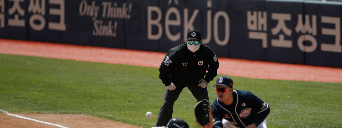 First base umpire Lee Gye-sung, center, wearing a mask and gloves as a precaution against the new coronavirus looks on during the pre-season baseball game between Doosan Bears and LG Twins in Seoul, South Korea, Tuesday, April 21, 2020. South Korea's professional baseball league has decided to begin its new season on May 5, initially without fans, following a postponement over the coronavirus. (AP Photo/Lee Jin-man)