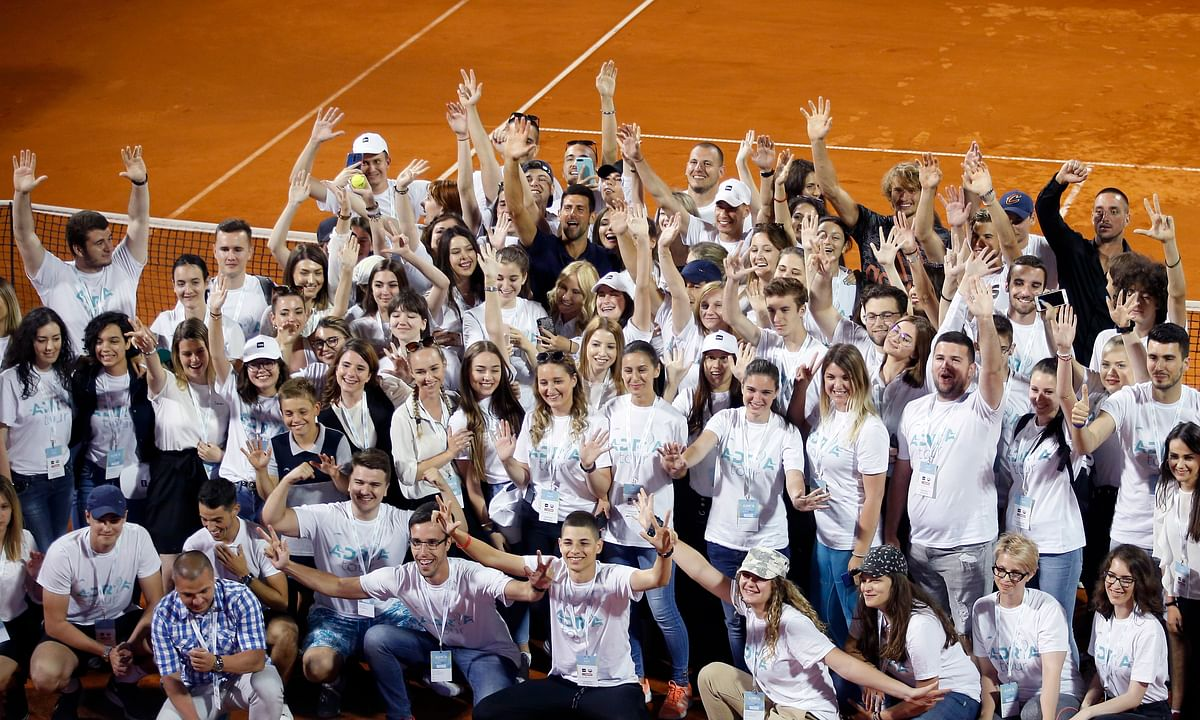 In this photo taken on Sunday, June 14, 2020, Serbia's Novak Djokovic, center, in blue, waves goodbye to safety protocols with volunteers and players after the Adria Tour charity tournament in Belgrade, Serbia. Two tennis players ranked among the top 40 in the world and five players at Serbia's biggest soccer club have tested positive for the virus after being involved in sporting events where fans packed into the stands and social distancing was not enforced. (AP Photo/Darko Vojinovic)