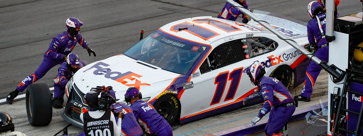 Denny Hamlin's pit crew performs a late pit stop during a NASCAR Cup Series auto race at Pocono Raceway, Sunday, June 28, 2020, in Long Pond, Pa.