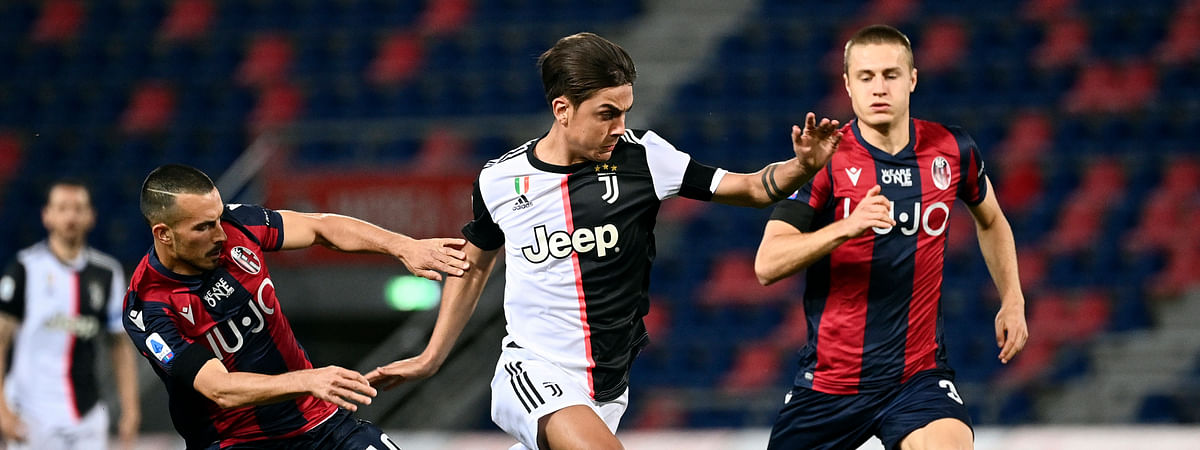 Juventus' Paulo Dybala, center, in action with Bologna's Nicola Sansone, left, during the Serie A soccer match between Bologna FC and Juventus FC at Stadio Renato Dall'Ara stadium in Bologna, Monday June 22, 2020.