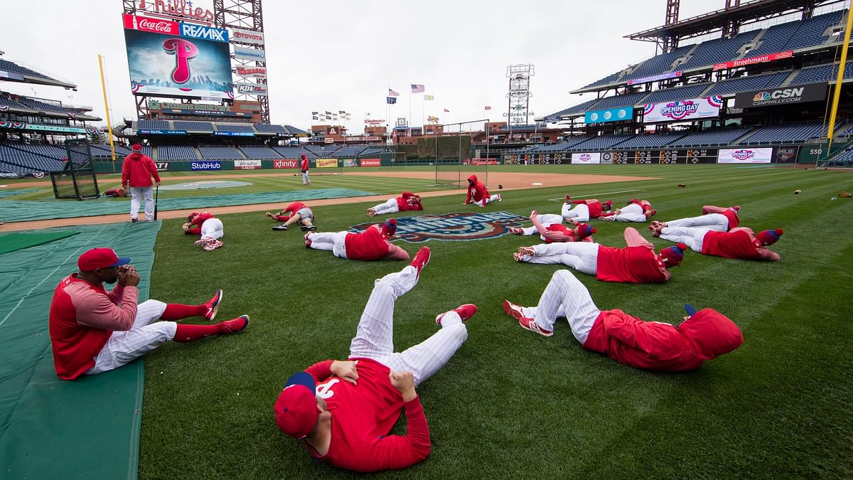 In this April 7, 2017, file photo, members of the Philadelphia Phillies stretch before the team's baseball game against the Washington Nationals in Philadelphia. Five players for the Philadelphia Phillies have tested positive for COVID-19 at the team's spring camp in Florida, prompting the club to indefinitely close the complex.The club didn't identify any of those affected.