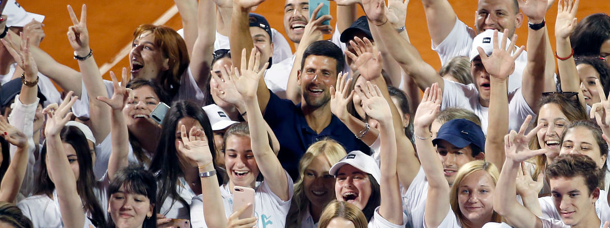 In this photo taken on Sunday, June 14, 2020, Serbia's Novak Djokovic, centre, poses with volunteers and players after the Adria Tour charity tournament in Belgrade, Serbia. Djokovic's charity tennis exhibition series combined with an overall softening of coronavirus restrictions in Serbia has led to a spike in the number the positive cases among professional athletes.