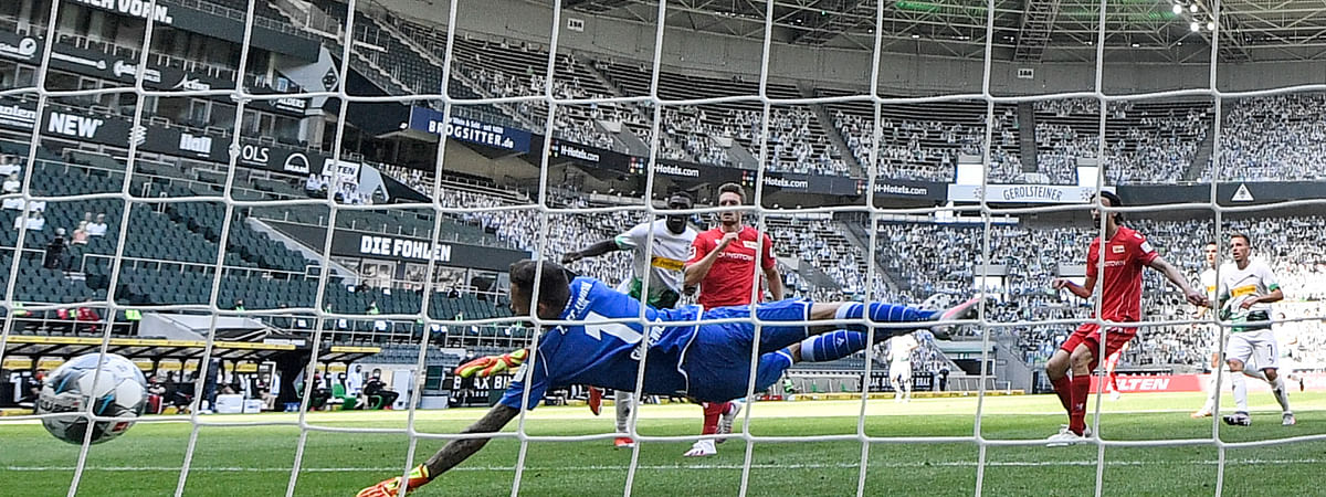 Moenchengladbach's Marcus Thuram, second left, scores his side's second goal against Berlin keeper Rafal Gikiewicz during the German Bundesliga soccer match between Borussia Moenchengladbach and Union Berlin in Moenchengladbach, Germany, Sunday, May 31, 2020.