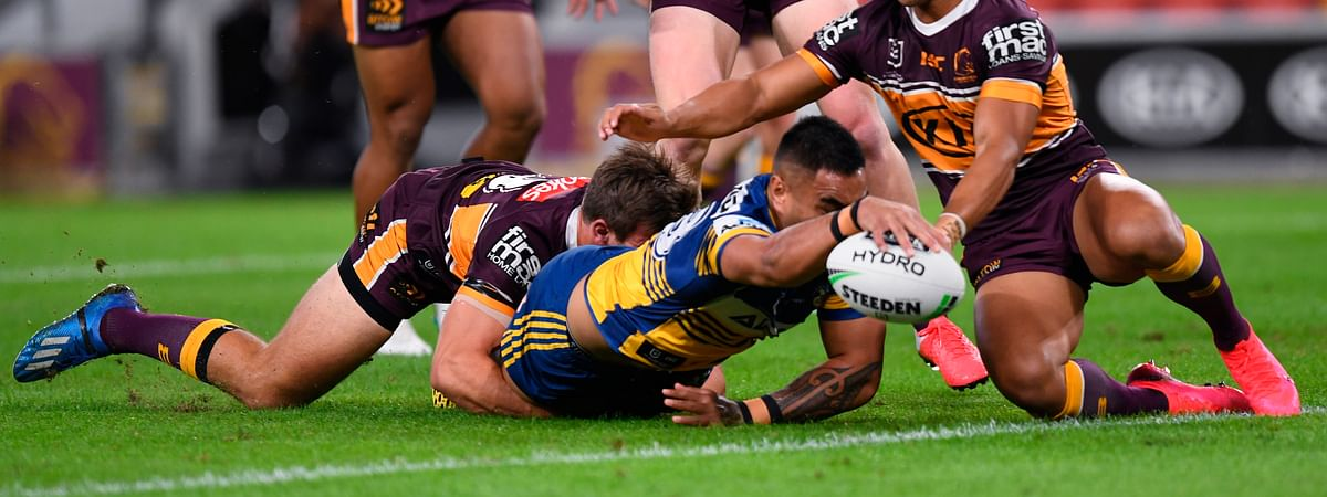 Marata Niukore, center, of the Parramatta Eels reaches out to score a try against the Brisbane Broncos as the National Rugby League resumes play, Thursday, May 28, 2020, in Brisbane, Australia.