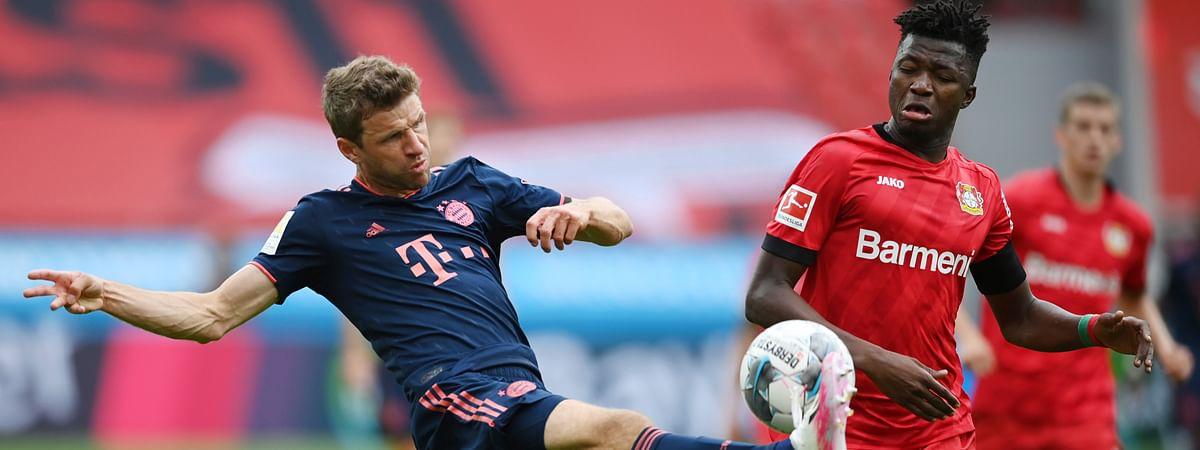 Thomas Mueller, left, of Munich is challenged by Edmond Tapsoda of Leverkusen during the German Bundesliga soccer match between Bayer Leverkusen and Bayern Munich in Leverkusen, Germany, Saturday, June 6, 2020.