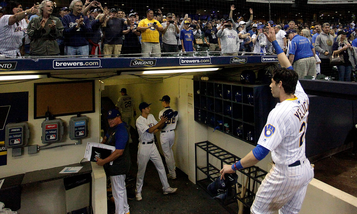 In this Sept. 7, 2019, file photo, fans cheer as Milwaukee Brewers' Christian Yelich walks off the field after driving in the winning run with a double during the ninth inning of the team's baseball game against the Chicago Cubs in Milwaukee.