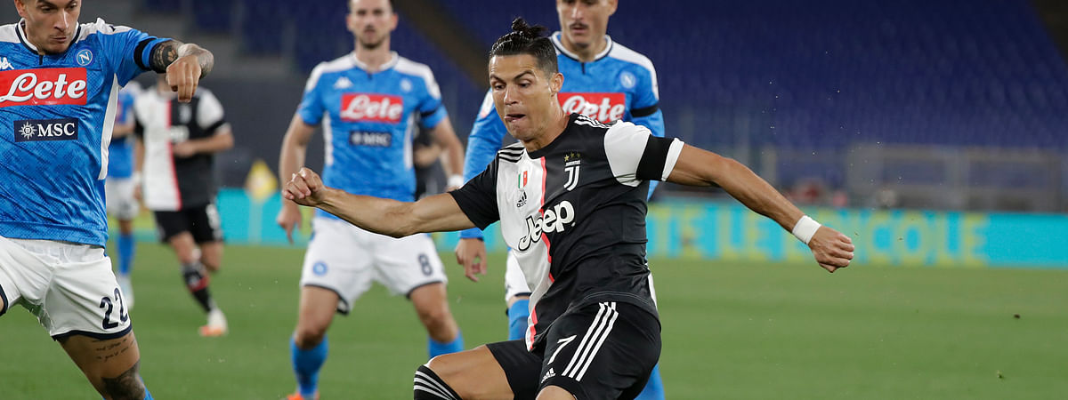 Juventus' Cristiano Ronaldo, right, kicks the ball as Napoli's Giovanni Di Lorenzo tries to stop him during the Italian Cup soccer final match between Napoli and Juventus, at Rome's Olympic Stadium, Wednesday, June 17, 2020.