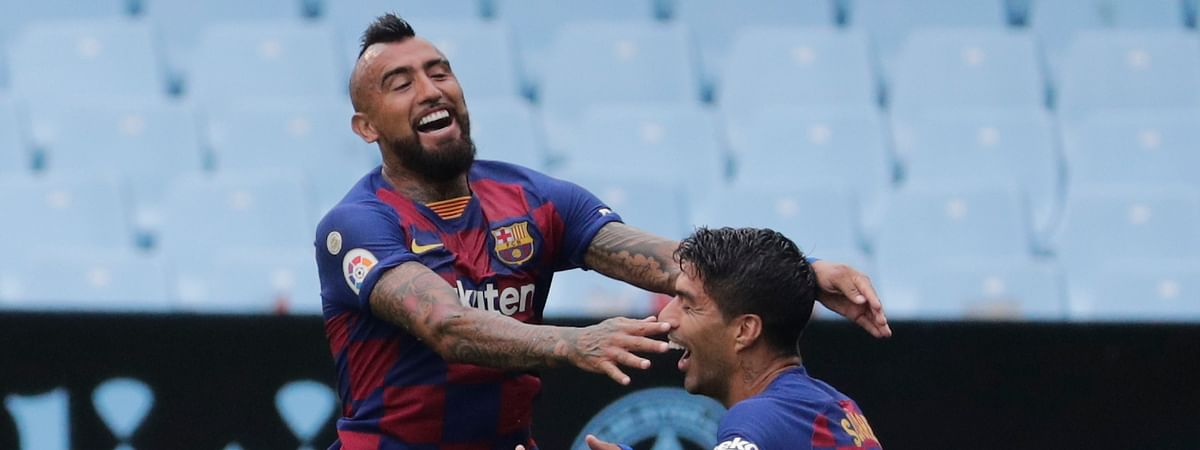 Barcelona's Luis Suarez, right, celebrates after with his teammate Barcelona's Arturo Vidal the opening goal during a Spanish La Liga soccer match between RC Celta and Barcelona at the Balaidos stadium in Vigo, Spain, Saturday, June 27, 2020.