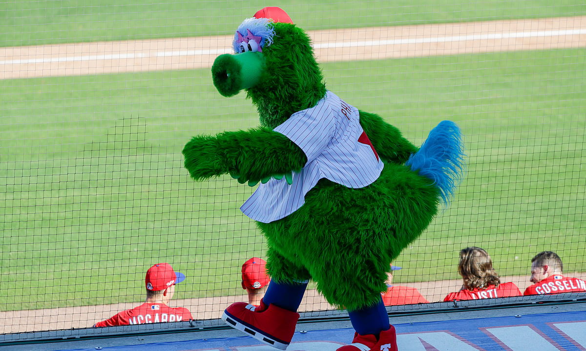 In this Feb. 23, 2020, file photo, the Phillie Phanatic mascot walks on the third-base dugout while the Philadelphia Phillies played the Pittsburgh Pirates in a spring training baseball game in Clearwater, Fla. Mascots are getting a reprieve from Major League Baseball. A month after being tossed out because of health concerns, they're again poised to become inside-the-parkers.