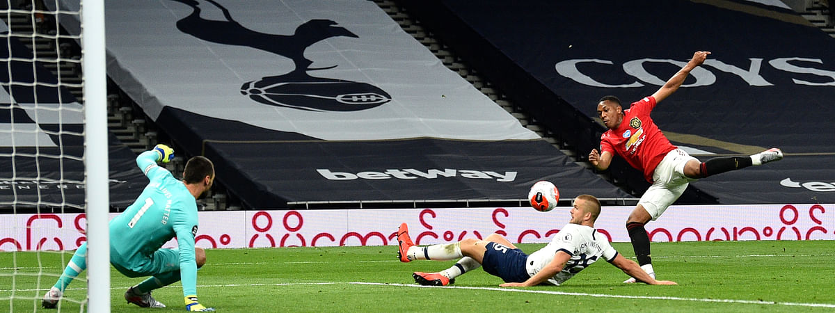 Manchester United's Anthony Martial, right, attempts a shot on goal during the English Premier League soccer match between Tottenham Hotspur and Manchester United at Tottenham Hotspur Stadium in London, England, Friday, June 19, 2020.