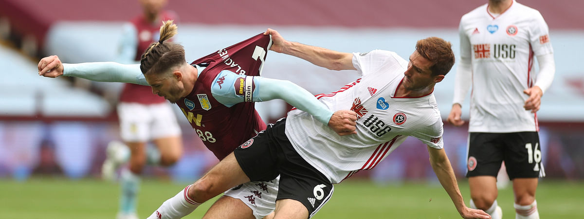 Aston Villa's Jack Grealish, left, challenges for the ball with Sheffield United's Chris Basham during the English Premier League soccer match between Aston Villa and Sheffield United at Villa Park in Birmingham, England, Wednesday, June 17, 2020. The English Premier League resumes Wednesday after its three-month suspension because of the coronavirus outbreak.