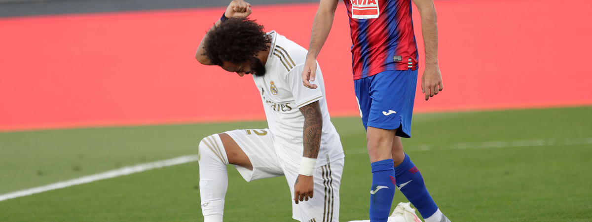 Real Madrid's Marcelo takes a knee as he celebrates his goal during the Spanish La Liga soccer match between Real Madrid and Eibar at Alfredo di Stefano stadium in Madrid, Spain, Sunday, June 14, 2020.