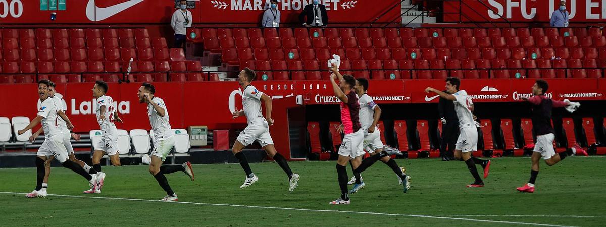 Sevilla players celebrate their Spanish La Liga soccer match victory against Betis in Seville, Spain, Thursday, June 11, 2020.
