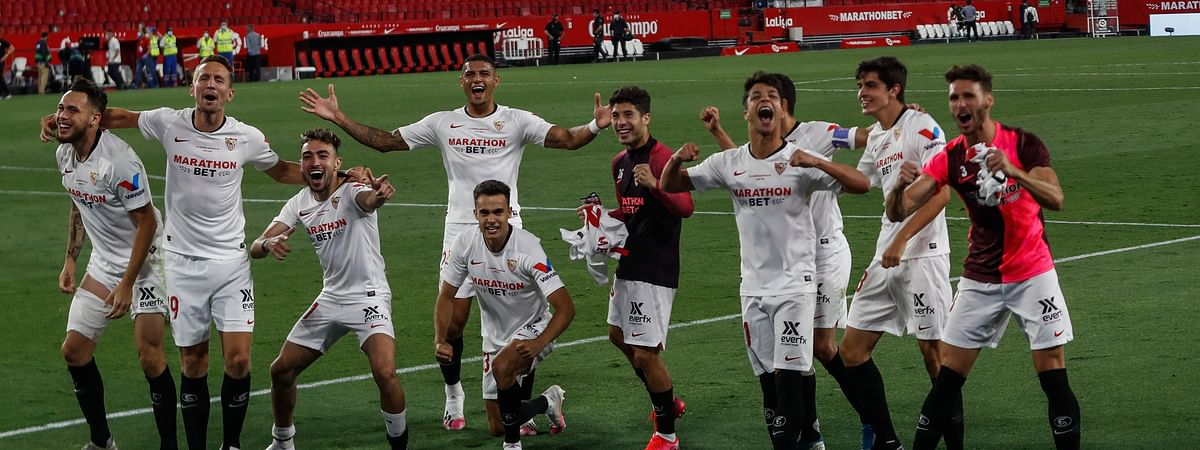 Sevilla players celebrate their Spanish La Liga soccer match victory against Betis in Seville, Spain, Thursday, June 11, 2020.