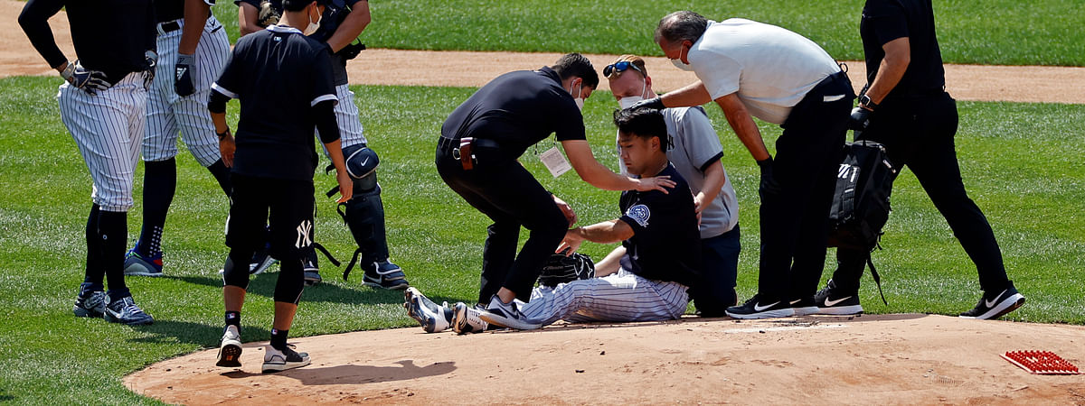 New York Yankees pitcher Masahiro Tanaka is tended to by team medical personnel after being hit by a ball off the bat of Yankees Giancarlo Stanton during a baseball a workout at Yankee Stadium in New York, Saturday, July 4, 2020.