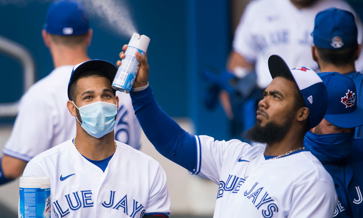 Toronto Blue Jays left fielder Lourdes Gurriel Jr., left, watches teammate Teoscar Hernandez, right, spray sanitizer in the dugout during the first inning of an intersquad baseball action in Toronto on Friday, July 17, 2020. The Blue Jays have been denied approval by the Canadian government to play in Toronto amid the coronavirus pandemic. Mark Eckel thinks the homeless Blue Jays won't be able to muster 28 wins this season.
