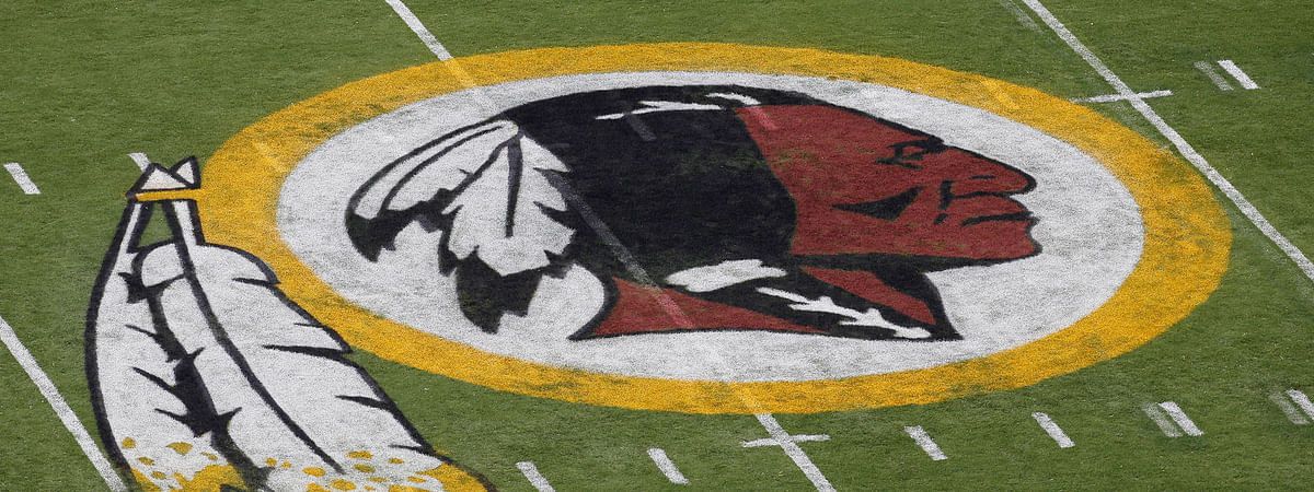 """In this Aug. 7, 2014 file photo, the Washington Redskins NFL football team logo is seen on the field before an NFL football preseason game against the New England Patriots in Landover, Md. The recent national conversation about racism has renewed calls for the Washington Redskins to change their name. D.C. mayor Muriel Bowser called the name an """"obstacle"""" to the team building its stadium and headquarters in the District."""