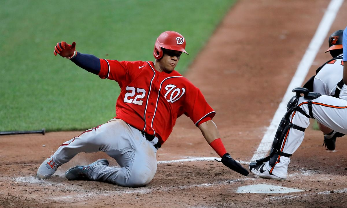 Washington Nationals' Juan Soto, left, slides in ahead of a tag by Baltimore Orioles catcher Austin Wynns while scoring on a double by Howie Kendrick during an exhibition baseball game Monday, July 20, 2020, in Baltimore.